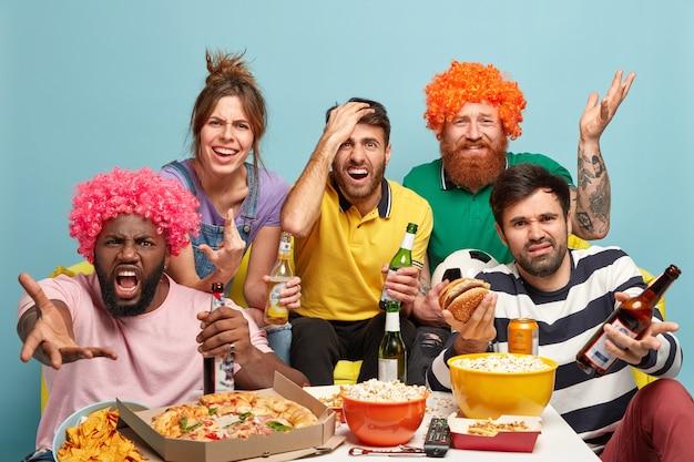 Rozczarowani czterej mężczyźni i jedna kobieta oglądają mecz, niezadowoleni z porażki zespołu, piją piwo, jedzą przekąskę, wyrażają negatywne reakcje, złe emocje, pozują razem na kanapie w domu. drużyna przegrywa.