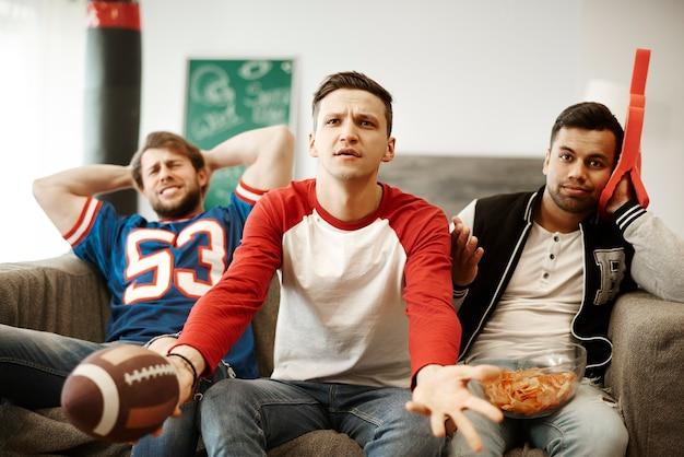 Rozczarowani fani piłki nożnej oglądający mecz z niedowierzaniem