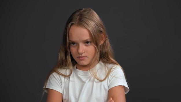 Rozczarowanie na twarzy uroczej małej dziewczynki z założonymi rękami, patrząc na przód w białej koszulce i czarnych spodniach odizolowanych na czarnej ścianie