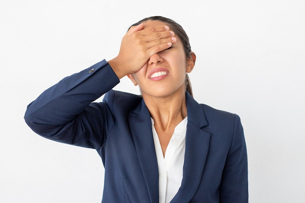 Rozczarowany bizneswoman z ręką na twarzy