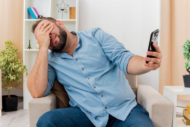 Rozczarowany dorosły słowiański mężczyzna siedzi na fotelu, kładąc dłoń na twarzy i trzymając telefon w salonie