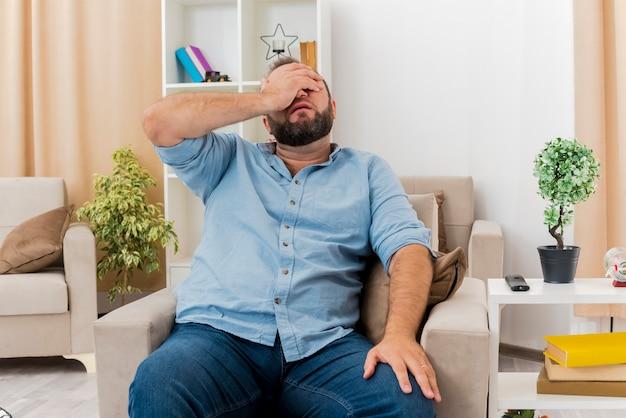 Rozczarowany dorosły słowiański mężczyzna siedzi na fotelu, kładąc dłoń na twarzy i zamykając oczy w salonie