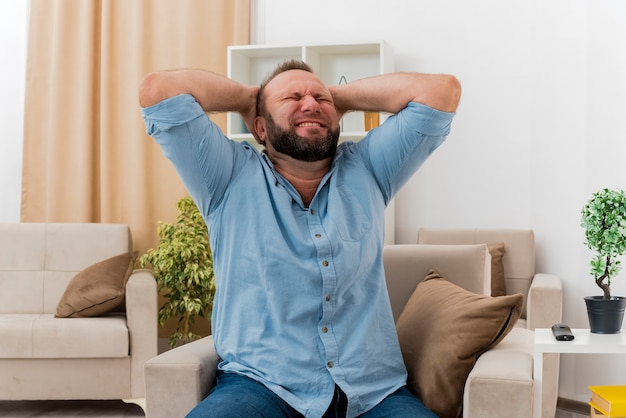 Rozczarowany dorosły słowiański mężczyzna siedzi w salonie na fotelu kładąc ręce na głowie z zamkniętymi oczami
