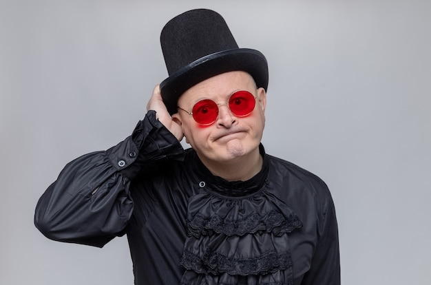 Rozczarowany dorosły słowiański mężczyzna w cylindrze i okularach przeciwsłonecznych w czarnej gotyckiej koszuli patrzący z przodu