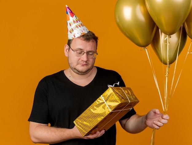 Rozczarowany dorosły słowiański mężczyzna w okularach optycznych w czapce urodzinowej trzyma balony z helem i pudełko upominkowe gift