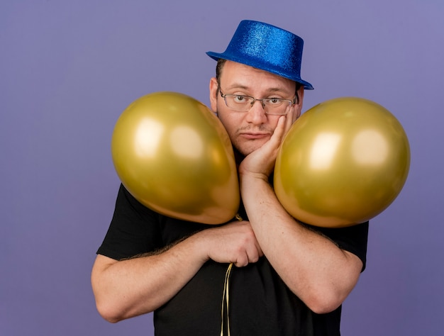 Rozczarowany dorosły słowiański mężczyzna w okularach optycznych w niebieskiej imprezowej czapce kładzie rękę na brodzie i trzyma balony z helem