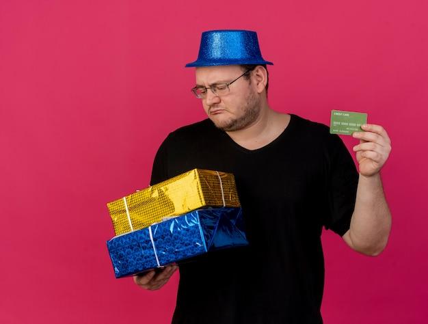 Rozczarowany dorosły słowiański mężczyzna w okularach optycznych w niebieskim kapeluszu imprezowym, trzyma pudełka na prezenty i kartę kredytową