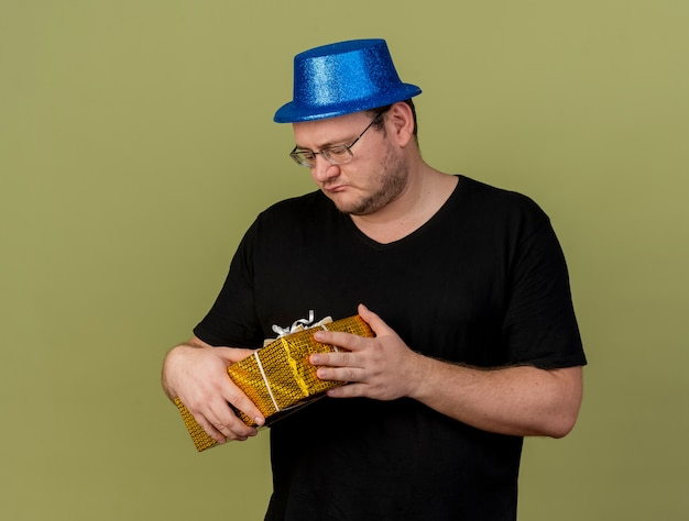 Rozczarowany dorosły słowiański mężczyzna w okularach optycznych w niebieskim kapeluszu imprezowym trzyma pudełko upominkowe
