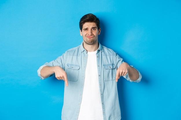 Rozczarowany facet w swobodnym stroju, wskazujący palcami w dół z wątpliwym grymasem, stojący pod niebieską ścianą
