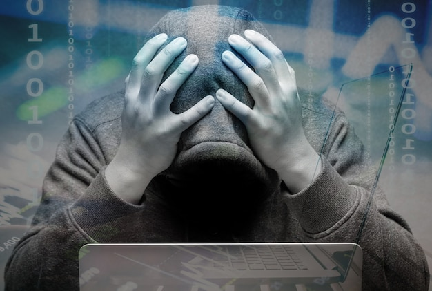 Rozczarowany haker z notebookiem komputerowym