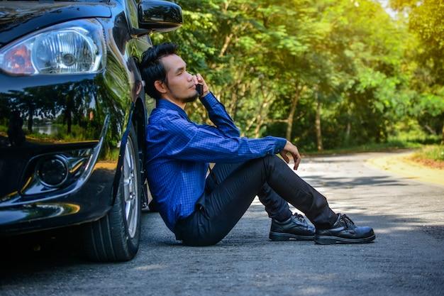 Rozczarowany mężczyzna trzyma mądrze telefon i obsiadanie przy samochodem parkującym na drodze
