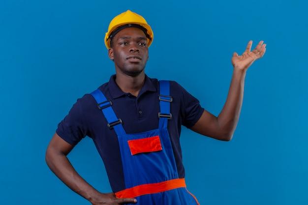 Rozczarowany młody afroamerykanin konstruktor w mundurze konstrukcyjnym i hełmie ochronnym, patrząc zdezorientowany stojąc z ręką uniesioną na niebiesko