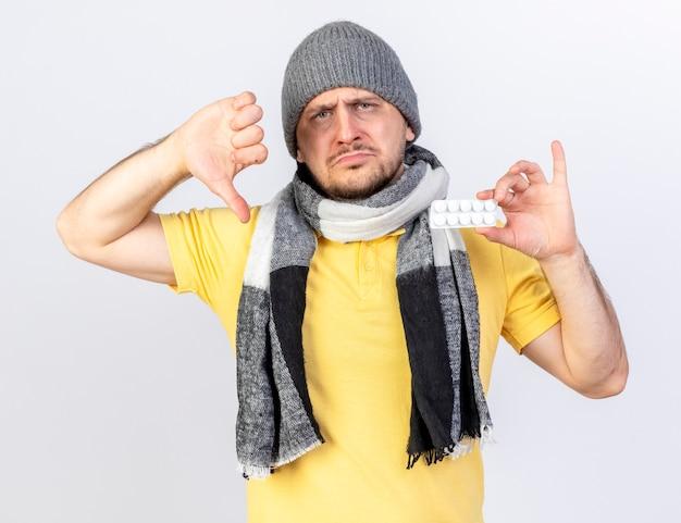 Rozczarowany młody blond chory słowiański mężczyzna w czapce zimowej i szaliku z kciukami w dół i trzyma paczkę tabletek medycznych na białej ścianie z miejscem na kopię