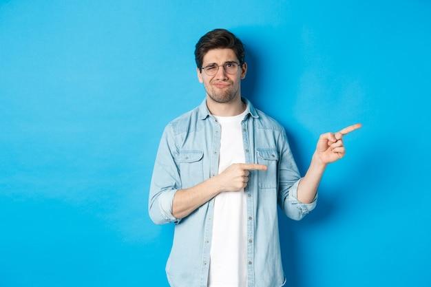 Rozczarowany młody człowiek w okularach, wskazujący palcami w prawo w miejsce kopii, pokazujący baner promocyjny i uśmiechający się niezadowolony, oceniający zły produkt, stojący na niebieskim tle.