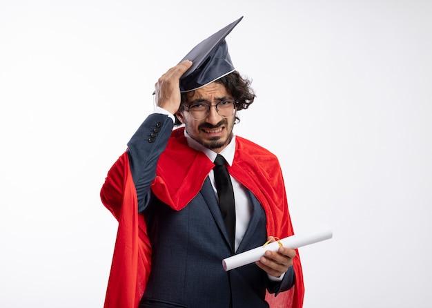 Rozczarowany młody kaukaski superbohater w okularach optycznych, ubrany w garnitur z czerwonym płaszczem i kładący rękę na czapce z dyplomem ukończenia studiów