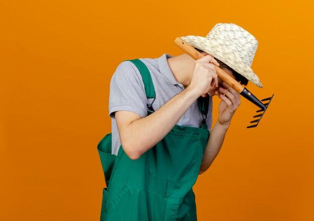 Rozczarowany młody męski ogrodnik w kapeluszu ogrodniczym kładzie rękę na twarzy i trzyma grabie