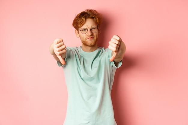 Rozczarowany młody mężczyzna w okularach z niechlujną czerwoną fryzurą, pokazujący kciuki w dół i krzywiący się z niezadowoleniem...