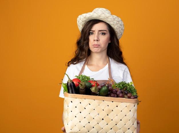 Rozczarowany młody ogrodnik kobiece w mundurze na sobie kapelusz ogrodniczy trzyma kosz warzyw na pomarańczowej ścianie