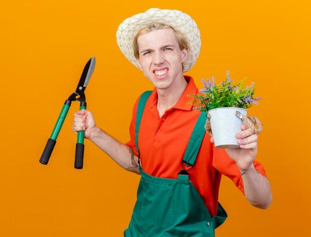 Rozczarowany młody ogrodnik w kombinezonie i kapeluszu trzymający nożyce do żywopłotu i roślinę doniczkową patrząc na kamerę niezadowolony stojąc na pomarańczowym tle