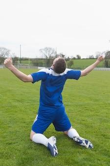 Rozczarowany piłkarz w niebieskim siedzi na boisku po przegranej