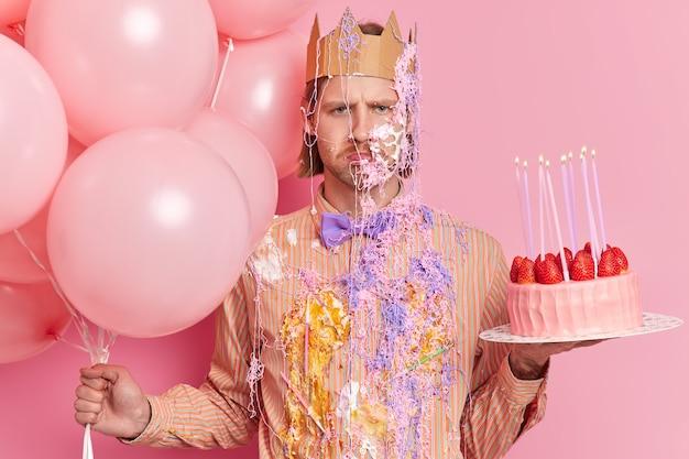 Rozczarowany, ponury zdenerwowany mężczyzna posmarowany kremem i wężowym sprayem, gotowy do świętowania urodzinowych poz z balonami powietrznymi i ciastem truskawkowym