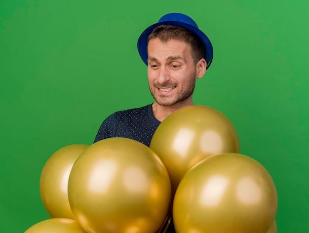 Rozczarowany przystojny mężczyzna ubrany w niebieski kapelusz partii trzyma i patrzy na balony z helem na białym tle na zielonej ścianie z miejsca na kopię