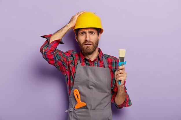 Rozczarowany robotnik ubrany w kask ochronny, zwykły mundur, trzyma pędzel do malowania, jest profesjonalnym malarzem, ma niezadowolony wyraz twarzy, odizolowany na fioletowej ścianie