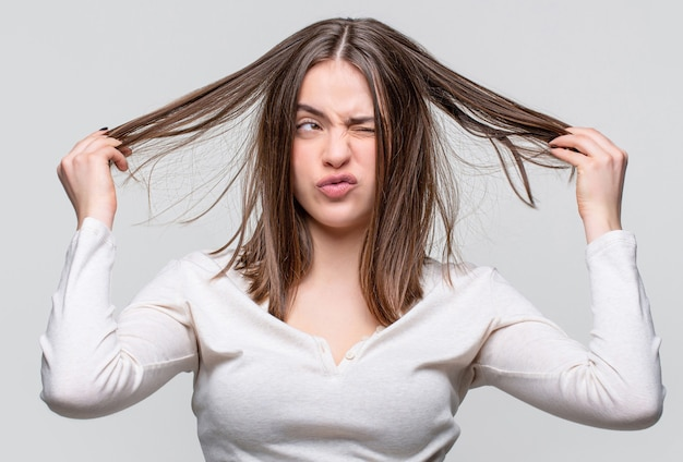 Rozczochrane włosy. brunetki kobieta z pomieszanymi włosami. dziewczyna ma złe włosy. dzień złych włosów