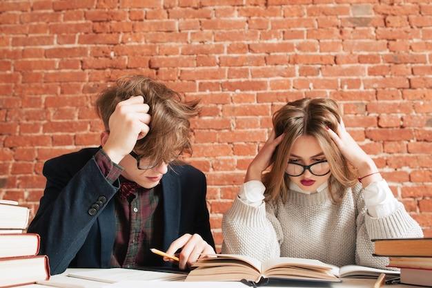 Rozczochrany mężczyzna i kobieta studiują w bibliotece