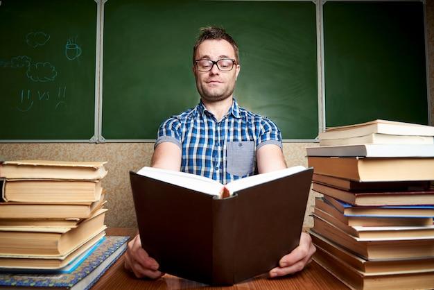 Rozczochrany młody człowiek czyta książkę przy stołem z stosami książki.