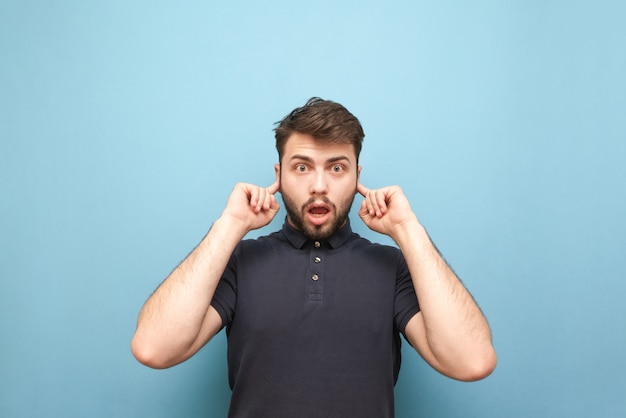 Rozczulony mężczyzna z zaskoczoną twarzą, zaciska uszy odizolowanymi na niebiesko palcami