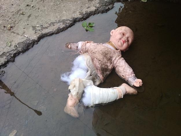 Rozdarta, zepsuta lalka w kałuży.