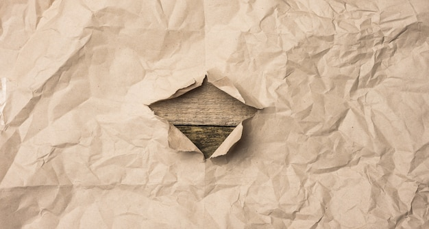 Rozdarty arkusz brązowego papieru z dziurą na drewnianym tle ze starych desek