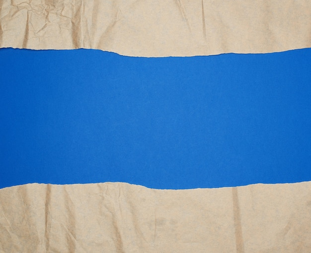 Rozdarty brązowy arkusz papieru na niebieskim tle, pełną klatkę