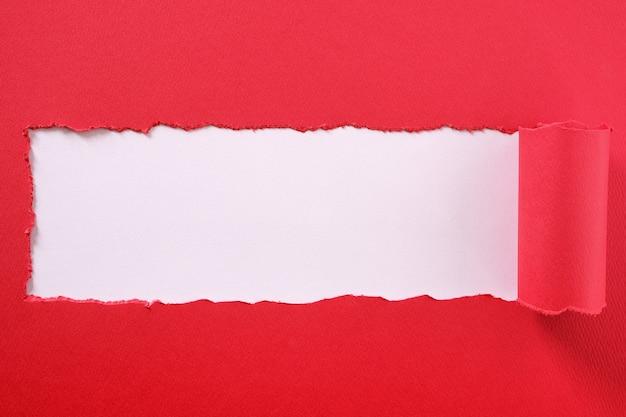 Rozdarty czerwony pasek papieru zwinięte krawędzi centrum ramy białe tło