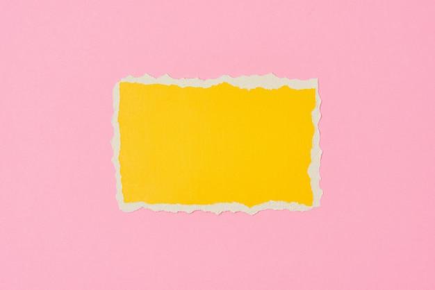 Rozdarty żółty papier rozdarty arkusz krawędzi na różowo. szablon z kawałkiem kolorowego papieru