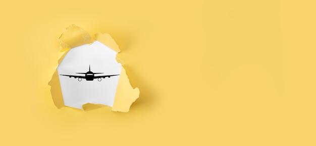 Rozdarty żółty papier z ikoną samolotu samolot na niebieskim tle. zakup biletu banner.nline. ikony podróży o planowanie podróży, transport, hotel, paszport lotniczy. koncepcja rezerwacji biletów lotniczych.