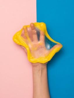 Rozdarty żółty szlam na dłoni na różowym i niebieskim tle. zabawka antystresowa. zabawka do rozwoju motoryki ręcznej.