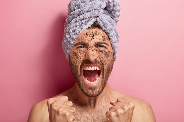 Rozdrażniony emocjonalnie młody człowiek podnosi zaciśnięte pięści, trzyma szeroko otwarte usta, zły na zabiegi kosmetyczne, ma nagie ciało, głowę owiniętą miękkim ręcznikiem
