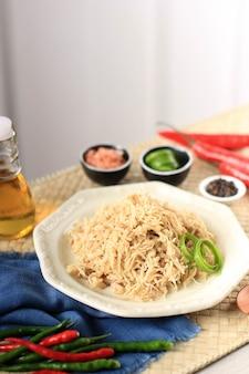 Rozdrobniony kurczak na talerzu śmietankowym, doprawiony różnymi ziołami. w indonezji zwykle używany do nadziewania lemper ayam