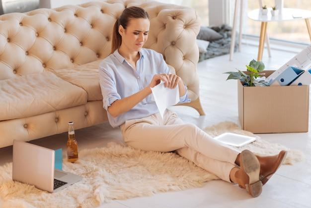 Rozdzierany papier. młoda nieszczęśliwa emocjonalna kobieta siedzi na podłodze z plecami opartymi na sofie i rozdziera papier, podczas gdy nowoczesne gadżety leżą na podłodze u jej boku