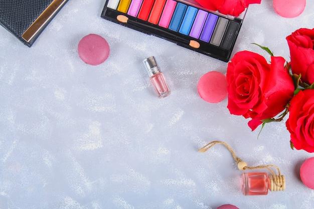 Róże, cień do oczu, torebka, perfumy, macaroons na szarym stole. płaskie leżało. widok z góry. rzeczy kobiece.
