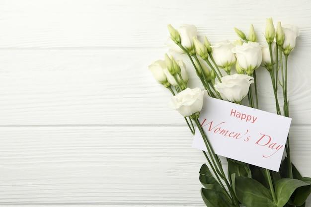 Róże i tekst szczęśliwy dzień kobiet na białym tle drewniane