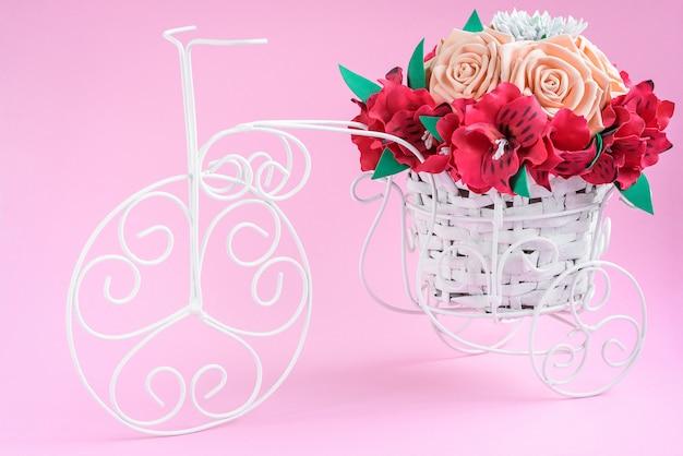 Róże kwiaty w ozdobnym białym rowerze na różowym tle. prezent świąteczny na ślub lub urodziny.