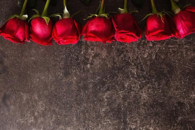 Róże leżą na ciemnym marmurowym stole. duży piękny bukiet czerwonych róż. kolory tekstur. prezent na ślub, urodziny, walentynki. miejsce na tekst i design. leżał płasko, lato.