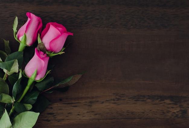Róże na ciemnym tle drewniane. miejsce do skopiowania. widok z góry.