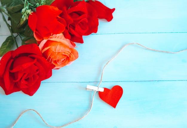 Róże na niebieskim tle i serca złapane sznurkiem. walentynki tło