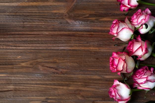 Róże obramiają na drewnianym brown tle