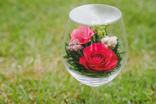 Róże ozdobiono przezroczystymi kieliszkami do wina na posadzce łąki. pomysły na prezenty dla zakochanych.