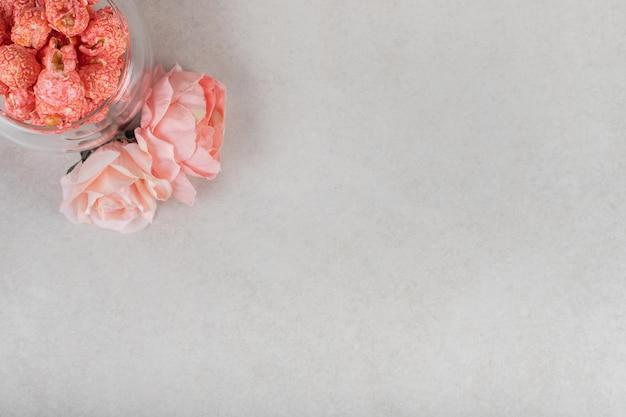 Róże przy małej misce czerwonego popcornu na marmurowym stole.